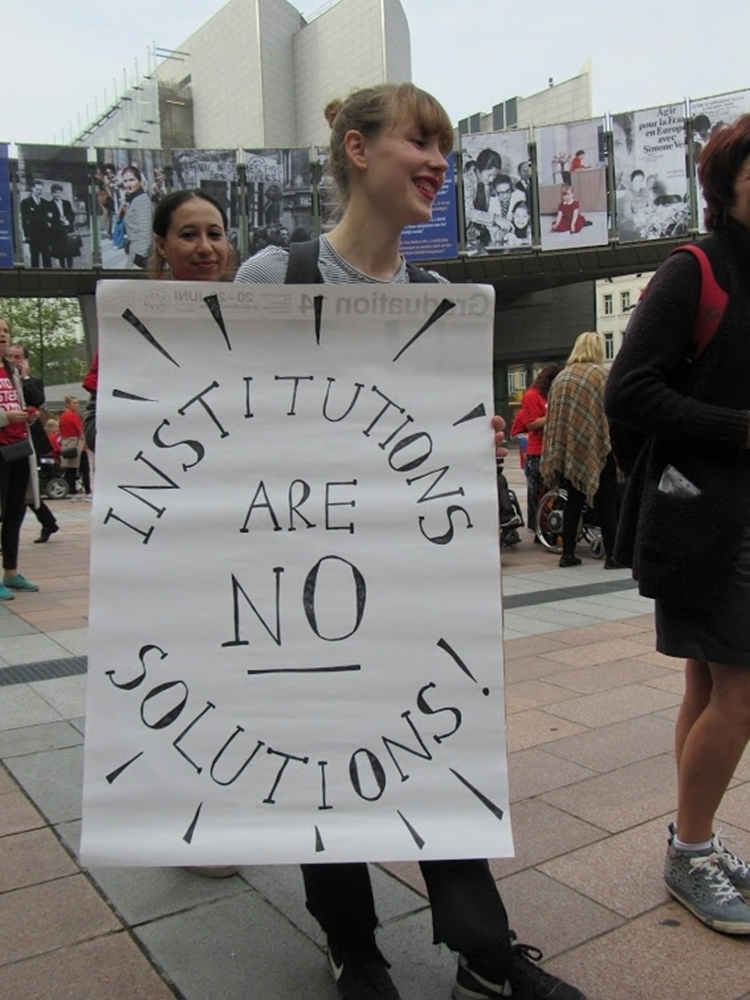 Vrouw met poster: Institutions are no solutions