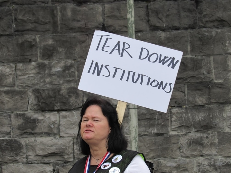 vrouw met bord: tear down institutions